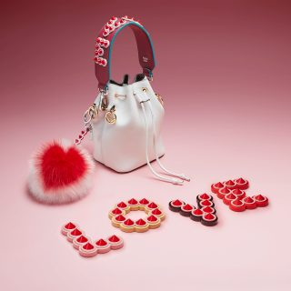 "Fendi's capsule collection for Saint Valentine this year stars the Mon Trésor mini bucket. The new cutie in the bag family finds its match in the Strap You dressed in red and punctuated with studs that spell ""LOVE"". And how can the furry Bag Bug charm miss out on all the action with its vibrant red heart?"