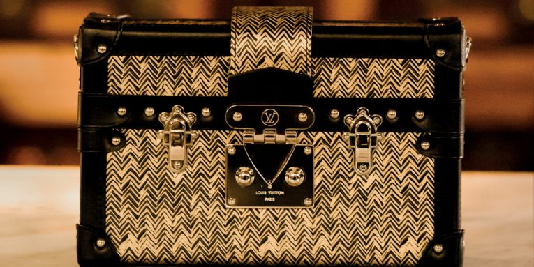 Louis Vuitton has pursued the Art of Travel with a plethora of luggage designs in countless combinations, pattern interpretations, materials, and shapes. Today, the trunks can be made-to-order for any travel needs but the classic trunk's detailing and silhouette continue to influence new creations. With the Bisten briefcase, for business, and the wildly popular Petite Malle, the woman's handbag, Louis Vuitton highlights the evolution of its trunks from travelling necessities to daily essentials. On the photo:  Bisten 55 briefcase in Monogram canvas; Bisten 50 in Monogram canvas (with personalization)