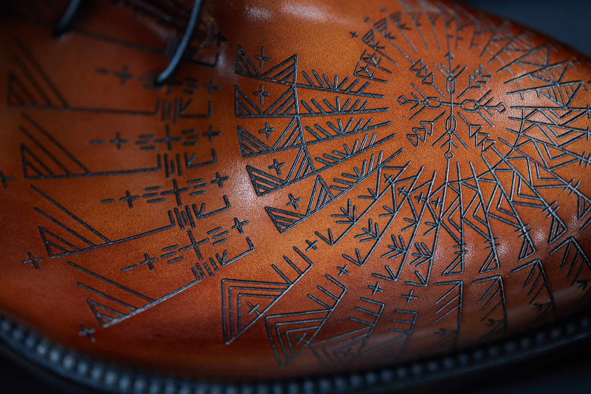 A DETAIL FROM A SHOE FEATURING A TATTOO