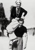 COCO CHANEL ON THE SHOULDERS OF HER FRIEND SERGE LIFAR