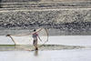 A fisherman casting his net into the river (Getty Images)