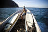 A surfer catching a boat ride at San Juan del Sur (credit: Corbis)