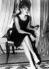 Romy Schneider wearing a Chanel black dress and two-tone shoes.