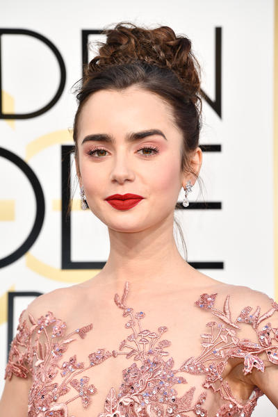 Lily Collins wears Vintage 1967 Winston Cluster Diamond Drop Earrings in platinum set with diamonds totalling 8.94ct and rings, all from Harry Winston