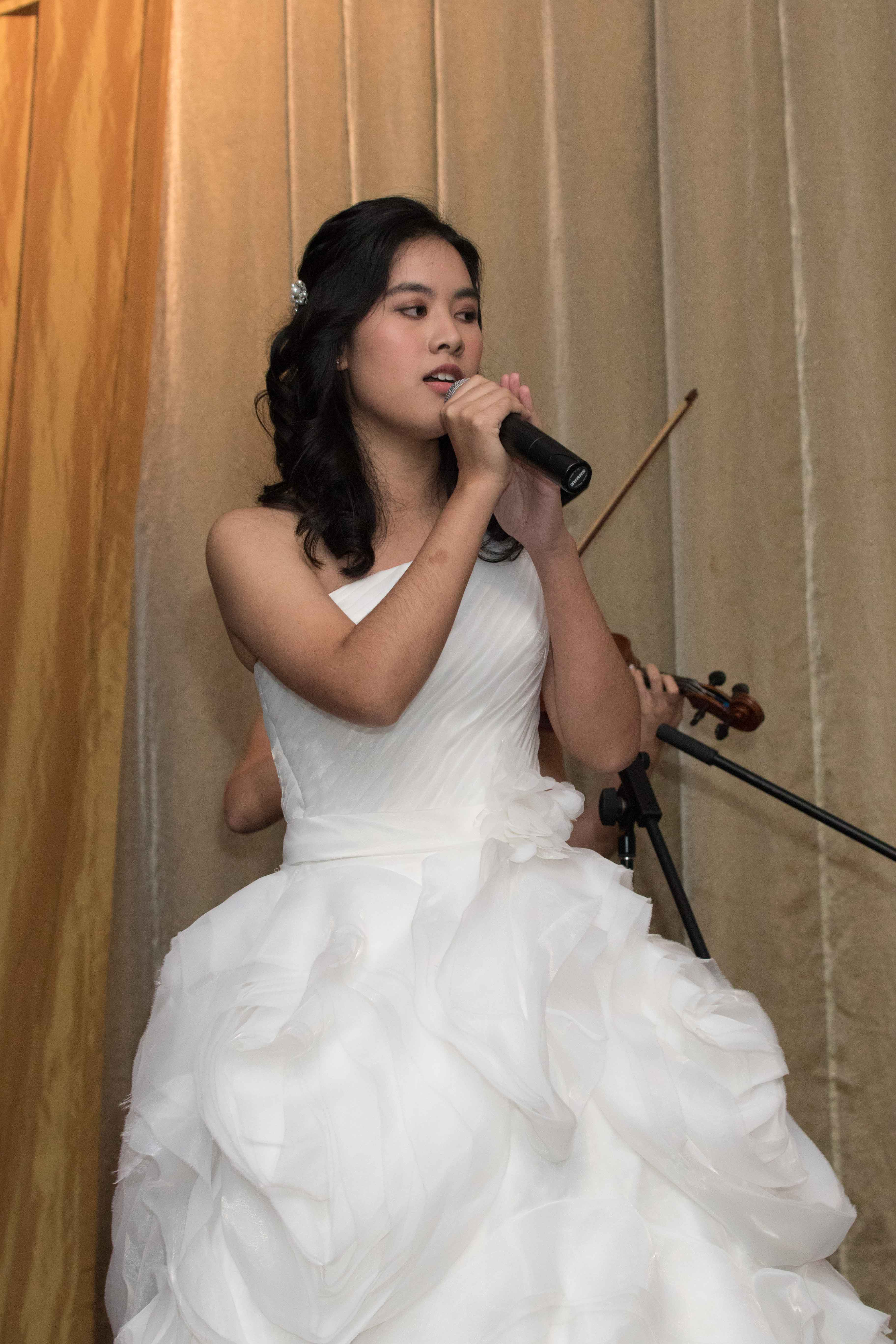 The bride, Isabelle Techawatanasuk, performs a song item ...