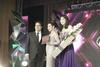 Prestige Award recipient Susanna Han receives her award from Tumi's Ashvin Valiram and Roses Only bouquet from Laura Lim