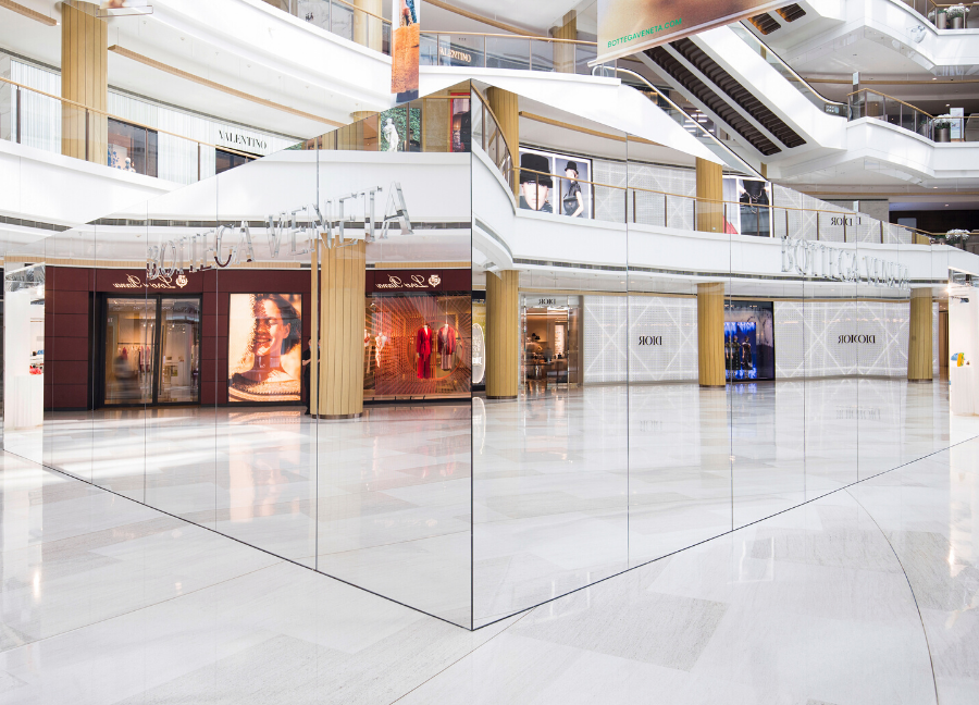 The Invisible Store is camouflaged by the reflections of logoed windows and signs inside the luxury mall's atrium
