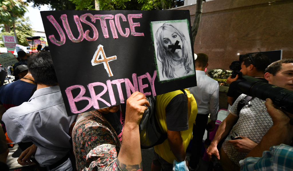 A fan holds a poster of the singer as supporters gather outside the Los Angeles County Courthouse on 14 July 2021 during a scheduled hearing.