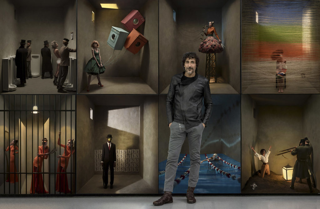 Eugenio Recuenco stands in front of a few of his lightbox images