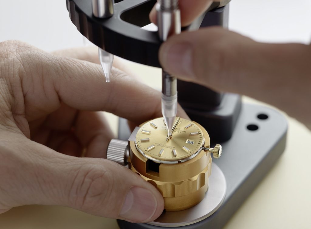 After remounting the dial on the movement, the watchmaker manually fits in the hands, one at a time.